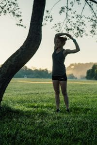 Runner stretching near tree